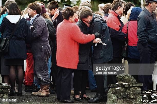 A crying won is comforted outside Dunblane primary school Scotland shortly after hearing the shooting incident on the premises The Dunblane school...