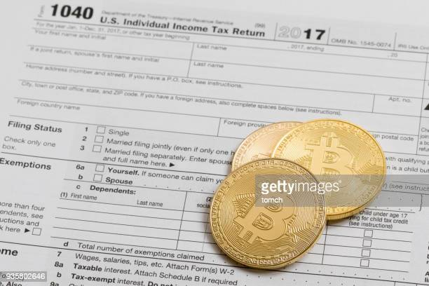 crypto-currencies against the backdrop of a tax return - 1040 tax form stock photos and pictures