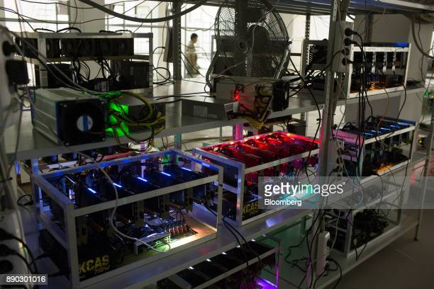 Cryptocurrency mining rigs operate on shelves linked to cryptocurrency mining machines at the SberBit mining 'hotel' in Moscow Russia on Saturday Dec...