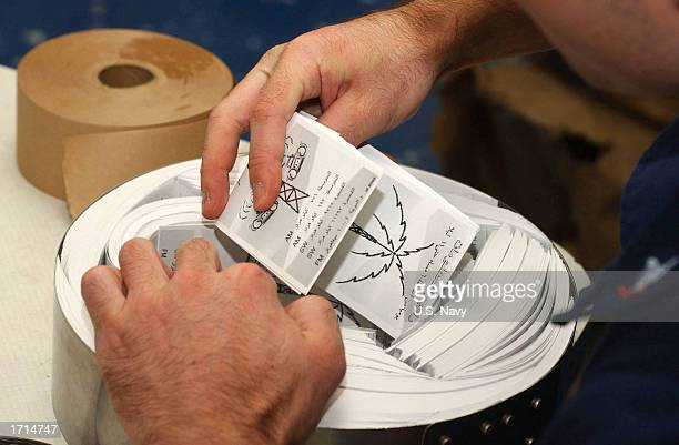 Cryptologic Technician 1st Class Steve Reed prepares leaflets for distribution to Iraqi military personnel in Iraq December 30 2002 while onboard the...
