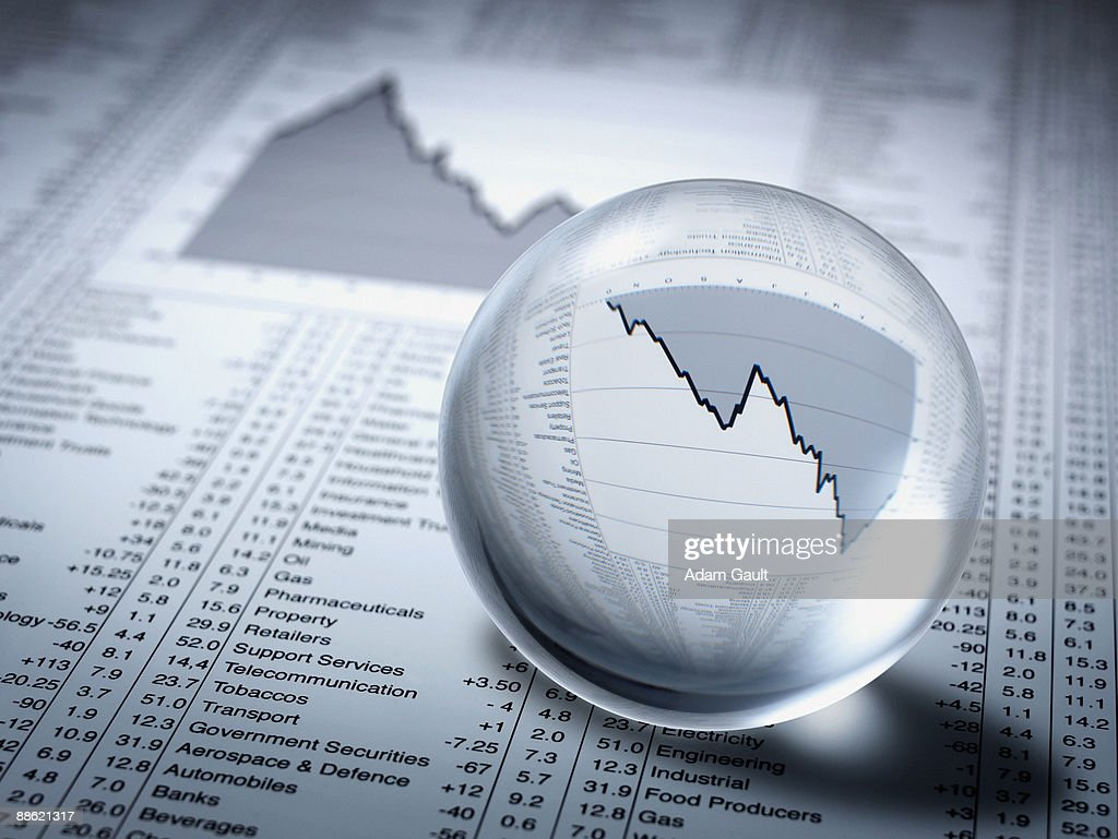 Crystal ball, descending line graph and share prices : Stock Photo
