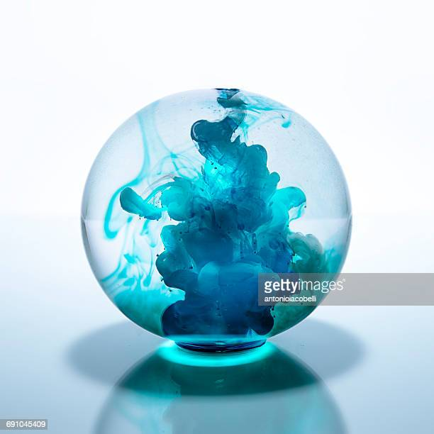 Crystal ball filled with blue watercolor paint in water