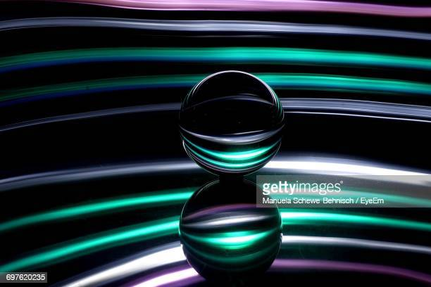 Crystal Ball On Glass Table Against Colored Background