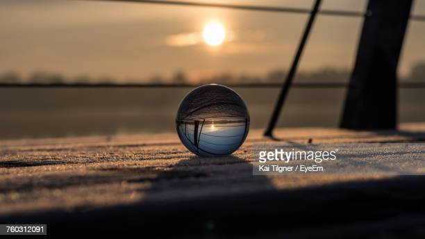 Crystal Ball On Retaining Wall Against Sky During Sunset