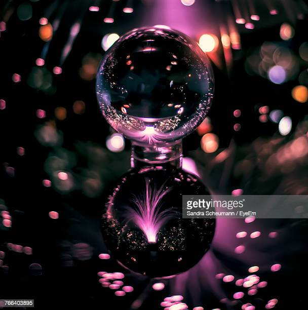 Crystal Ball On Table With Reflection Of Firework Display