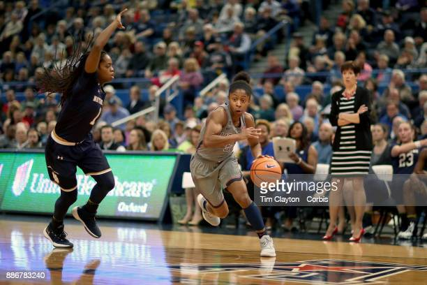 Crystal Dangerfield of the Connecticut Huskies drives past Lili Thompson of the Notre Dame Fighting Irish during the the UConn Huskies Vs Notre Dame...