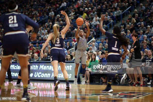 Crystal Dangerfield of the Connecticut Huskies hits a three point basket while defended by Marina Mabrey of the Notre Dame Fighting Irish and Lili...