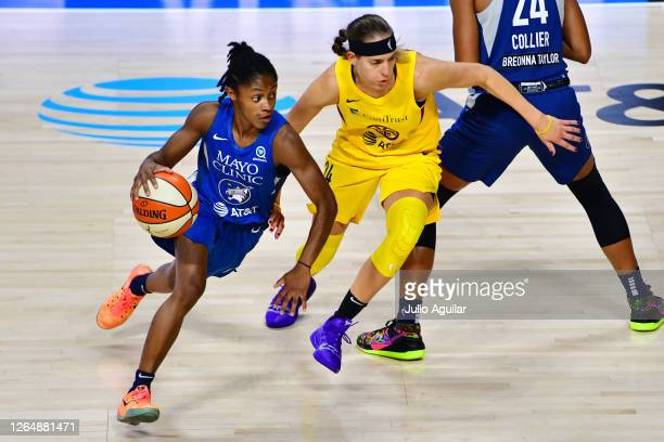 Crystal Dangerfield of the Minnesota Lynx dribbles up the court guarded by Sydney Wiese of the Los Angeles Sparks during the first half of a game at...
