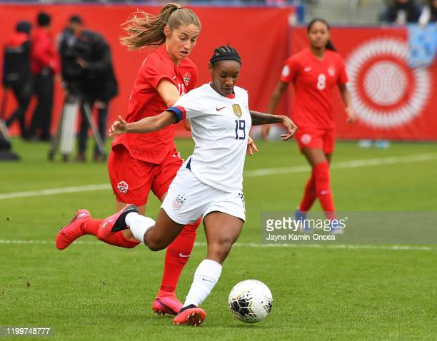 Crystal Dunn of the United States battles for the ball with Janine Beckie of Canada in the first half of the CONCACAF Women's Olympic Qualifying...