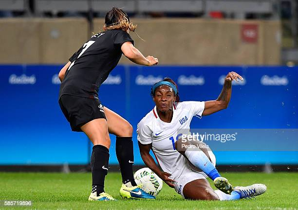 Crystal Dunn of United States falls while battling for the ball against Ali Riley of New Zealand in the Women's Group G first round match between the...