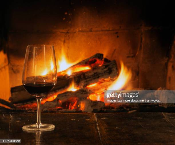 a crystal glass with red wine besides a burning fire of a fireplace. still life - warming up stock pictures, royalty-free photos & images