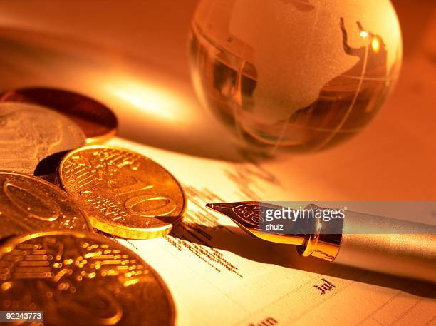 Crystal globe, coins and fountain pen on the stock page