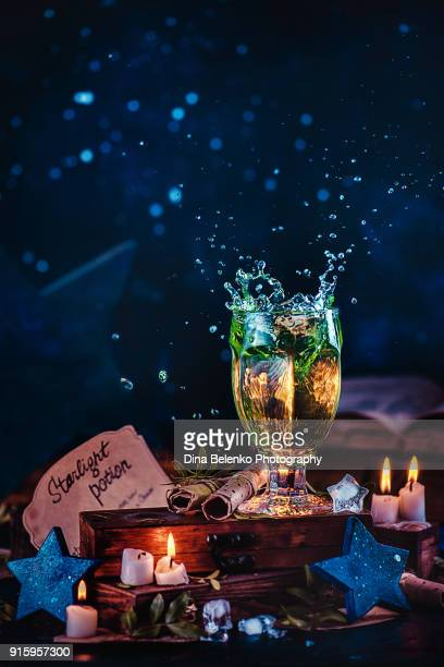 Crystal goblet with a splash of magical starlight potion with star-shaped ice cubes, wooden stars, ancient scrolls and burning candles. Conceptual still life photography. Magical scene with copy space.