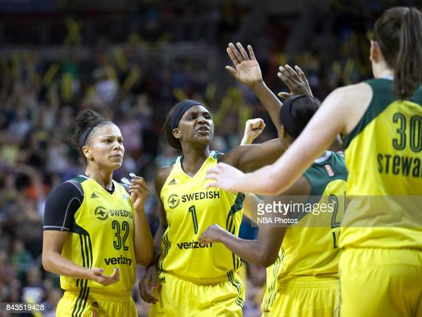 Crystal Langhorne of the Seattle Storm gives high fives to teammates during a WNBA game against the Phoenix Mercury on August 27 2017 at Key Arena in...