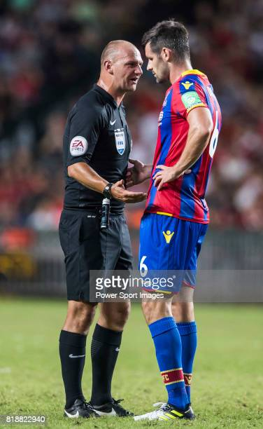 Crystal Palace defender Scott Dann argues with referee Bobby Madley during the Premier League Asia Trophy match between Liverpool FC and Crystal...