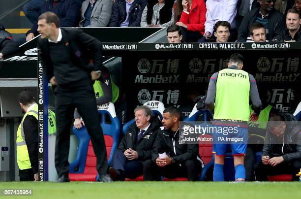 Crystal Palace manager Roy Hodgson sits in the dugout behind West Ham United manager Slaven Bilic on the touchline during the Premier League match at...