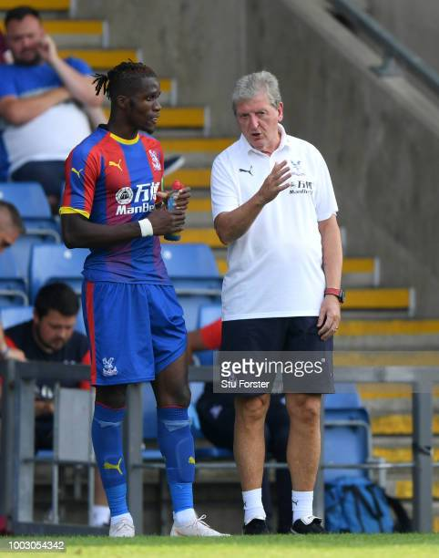 Crystal Palace manager Roy Hodgson talks with striker Wilfried Zaha during a Pre-Season Friendly match between Oxford United and Crystal Palce at...