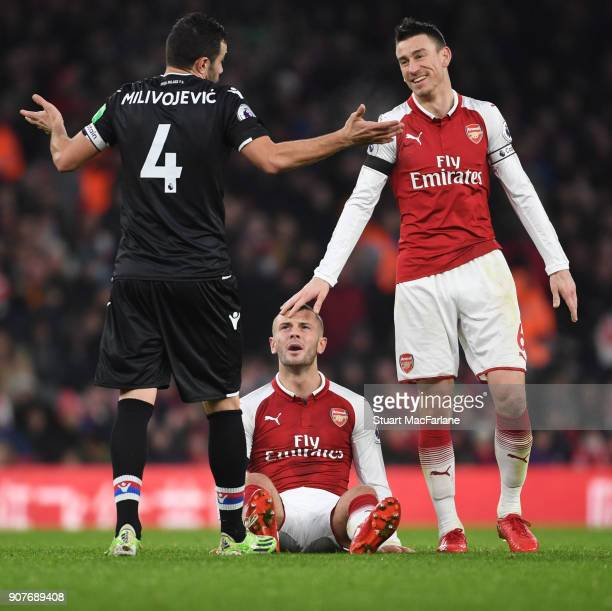 Crystal Palace midfielder Luka Milivojevic holds his hands up after and fous on Arsenal's Jack Wilshere and captain Lauren Koscielny sees the funny...