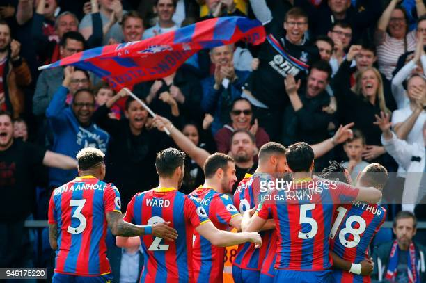 Crystal Palace players celebrate the opening goal scored by Crystal Palace's Ivorian striker Wilfried Zaha during the English Premier League football...