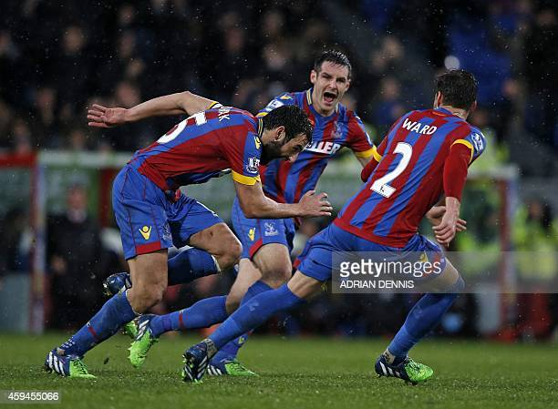 Crystal Palace's Australian midfielder Mile Jedinak celebrates with teammates after scoring their third goal from a freekick during the English...