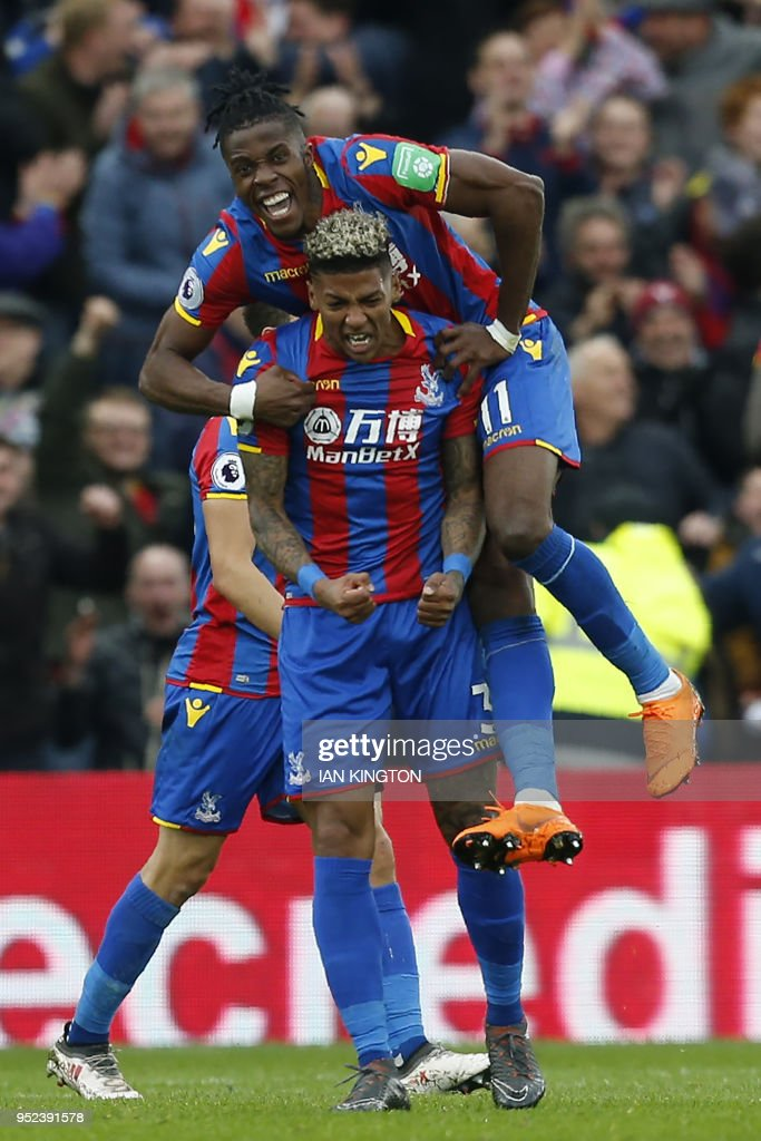 Crystal Palace's Dutch defender Patrick van Aanholt (C) celebrates scoring a goal with Crystal Palace's Ivorian striker Wilfried Zaha (top) during the English Premier League football match between Crystal Palace and Leicester City at Selhurst Park in south London on April 28, 2018. (Photo by Ian KINGTON / AFP) / RESTRICTED TO EDITORIAL USE. No use with unauthorized audio, video, data, fixture lists, club/league logos or 'live' services. Online in-match use limited to 75 images, no video emulation. No use in betting, games or single club/league/player publications. /
