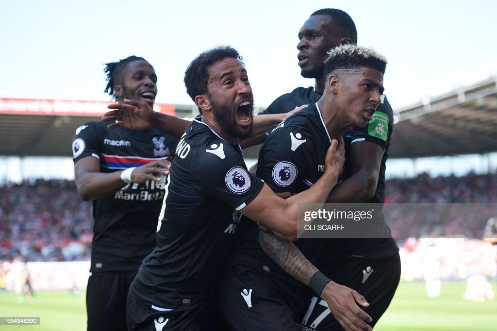 Crystal Palace's Dutch defender Patrick van Aanholt (R) celebrates scoring his team's second goal with Crystal Palace's Ivorian striker Wilfried Zaha (L) Crystal Palace's English midfielder Andros Townsend (2L) and Crystal Palace's Zaire-born Belgian striker Christian Benteke during the English Premier League football match between Stoke City and Crystal Palace at the Bet365 Stadium in Stoke-on-Trent, central England on May 5, 2018. (Photo by Oli SCARFF / AFP) / RESTRICTED TO EDITORIAL USE. No use with unauthorized audio, video, data, fixture lists, club/league logos or 'live' services. Online in-match use limited to 75 images, no video emulation. No use in betting, games or single club/league/player publications. /