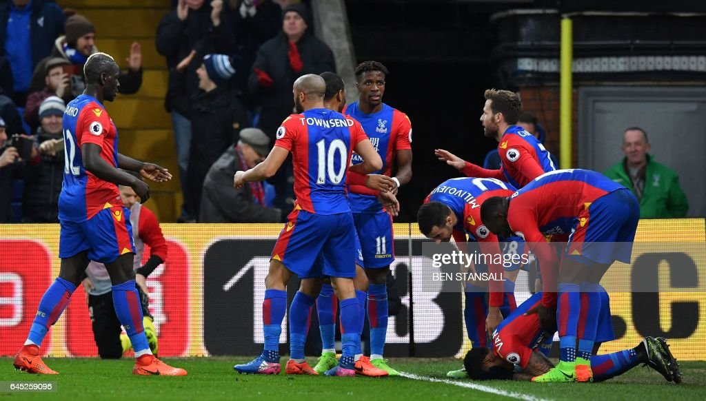 Crystal Palace's Dutch defender Patrick van Aanholt (2R) kneels on the pitch as he celebrates scoring his team's first goal during the English Premier League football match between Crystal Palace and Middlesbrough at Selhurst Park in south London on February 25, 2017. / AFP / Ben STANSALL / RESTRICTED TO EDITORIAL USE. No use with unauthorized audio, video, data, fixture lists, club/league logos or 'live' services. Online in-match use limited to 75 images, no video emulation. No use in betting, games or single club/league/player publications. /