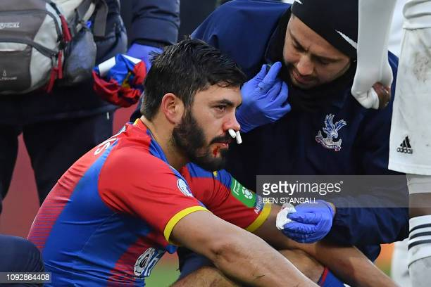 Crystal Palace's English defender James Tomkins receives medical attention for an injury during the English Premier League football match between...