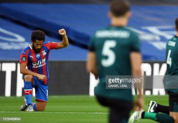 Crystal Palace's English midfielder Andros Townsend takes a knee in support of the Black Lives Matter movement during the English Premier League...