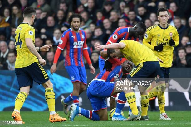 Crystal Palace's Frenchborn Ghanaian striker Jordan Ayew collides with Arsenal's Greek defender Sokratis Papastathopoulos during the English Premier...