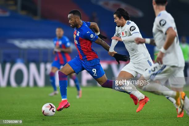 Crystal Palace's French-born Ghanaian striker Jordan Ayew fights for the ball with Leeds United's Dutch defender Pascal Struijk during the English...