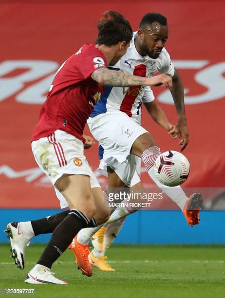 Crystal Palace's Frenchborn Ghanaian striker Jordan Ayew plays the ball as Manchester United's Swedish defender Victor Lindelof defends during the...