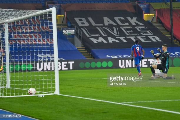Crystal Palace's French-born Ghanaian striker Jordan Ayew scores as Leeds United's French goalkeeper Illan Meslier reacts during the English Premier...