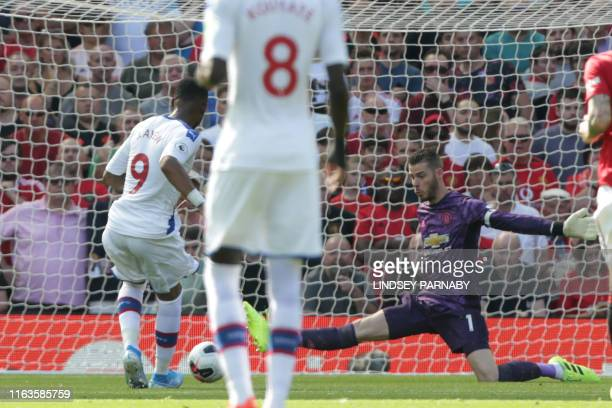 Crystal Palace's Frenchborn Ghanaian striker Jordan Ayew shoots past Manchester United's Spanish goalkeeper David de Gea to score the opening goal...