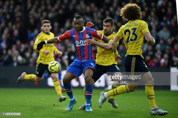 Crystal Palace's Frenchborn Ghanaian striker Jordan Ayew vies with Arsenal's Greek defender Sokratis Papastathopoulos during the English Premier...