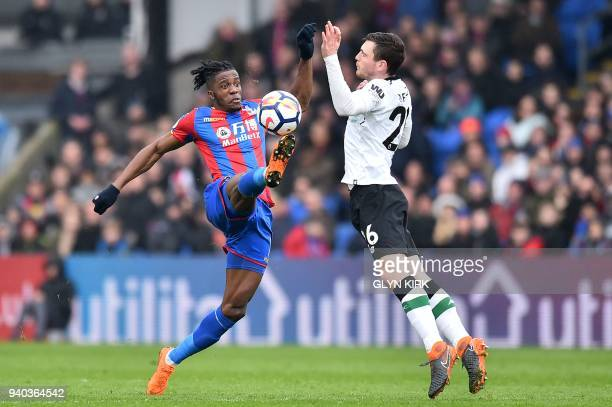 TOPSHOT Crystal Palace's Ivorian striker Wilfried Zaha and Liverpool's Scottish defender Andrew Robertson vie for the ball during the English Premier...