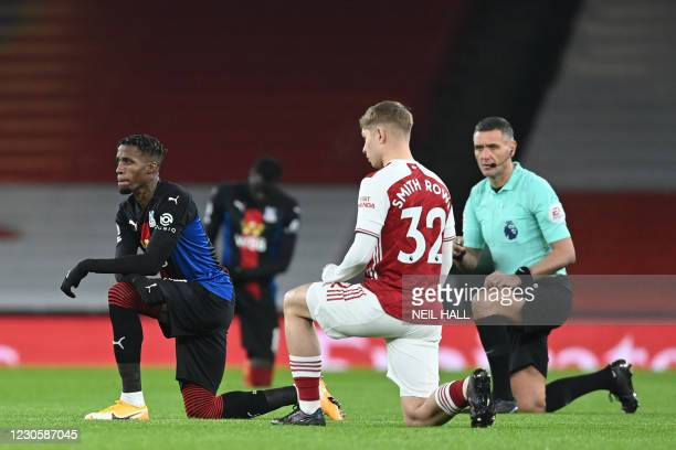 Crystal Palace's Ivorian striker Wilfried Zaha , Arsenal's English midfielder Emile Smith Rowe and English referee Andre Marriner 'take a knee' in...
