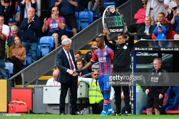 Crystal Palace's Ivorian striker Wilfried Zaha comes on as a substitute and shakes hands with Crystal Palace's English manager Roy Hodgson during the...