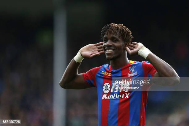 Crystal Palace's Ivorian striker Wilfried Zaha gestures to supporters during the English Premier League football match between Crystal Palace and...