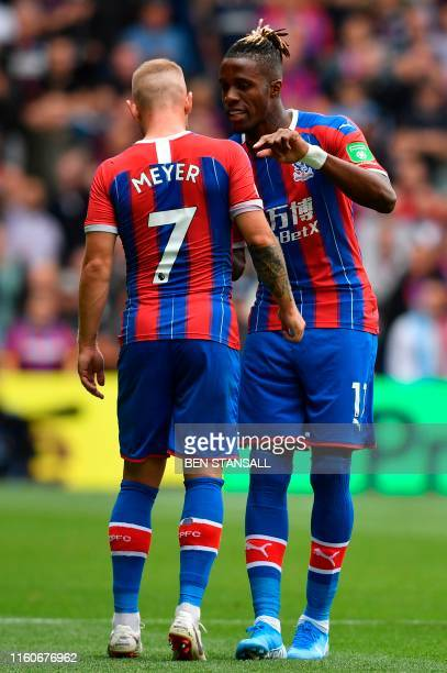 Crystal Palace's Ivorian striker Wilfried Zaha give instructions from Crystal Palace's German midfielder Max Meyer after coming on as a substitute...