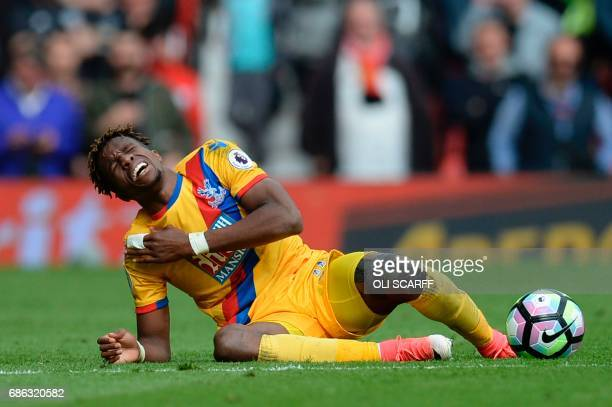 Crystal Palace's Ivorian striker Wilfried Zaha goes down after a challenge during the English Premier League football match between Manchester United...