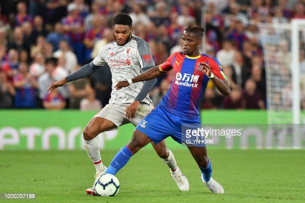 Crystal Palace's Ivorian striker Wilfried Zaha is challenged by Liverpool's English defender Joe Gomez during the English Premier League football...