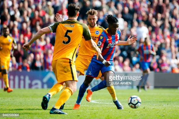 Crystal Palace's Ivorian striker Wilfried Zaha powers past Brighton's English midfielder Dale Stephens during the English Premier League football...