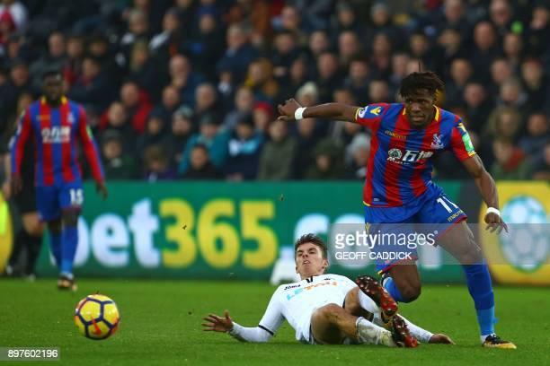 Crystal Palace's Ivorian striker Wilfried Zaha runs away from Swansea City's English midfielder Tom Carroll during the English Premier League...