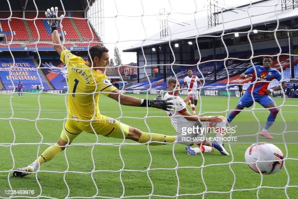 Crystal Palace's Ivorian striker Wilfried Zaha scores the opening goal past Southampton's English goalkeeper Alex McCarthy during the English Premier...