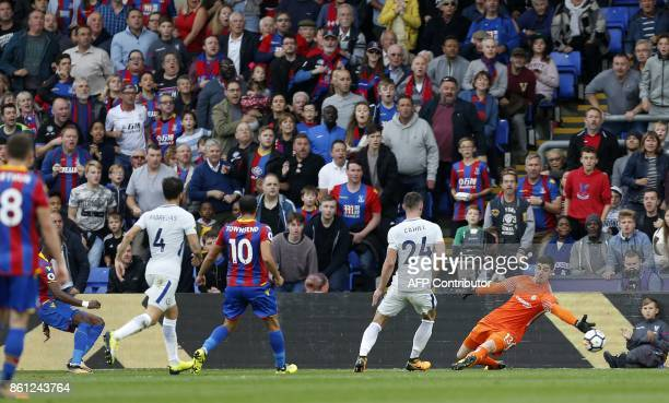 Crystal Palace's Ivorian striker Wilfried Zaha shoots past Chelsea's Belgian goalkeeper Thibaut Courtois to score their second goal during the...