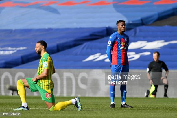Crystal Palace's Ivorian striker Wilfried Zaha stands as players 'take the knee' ahead of the English Premier League football match between Crystal...