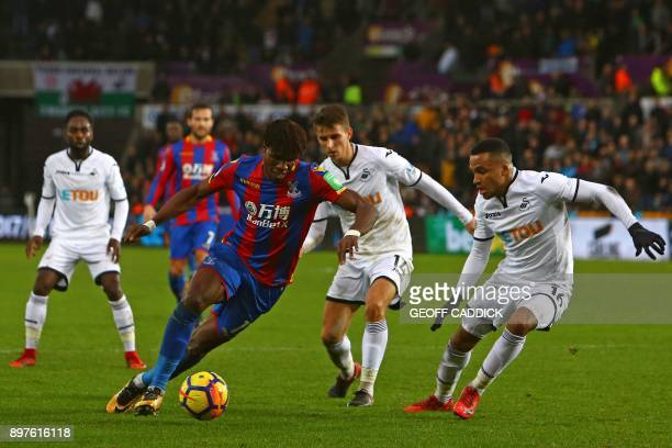 Crystal Palace's Ivorian striker Wilfried Zaha takes on the Swansea defence during the English Premier League football match between Swansea City and...