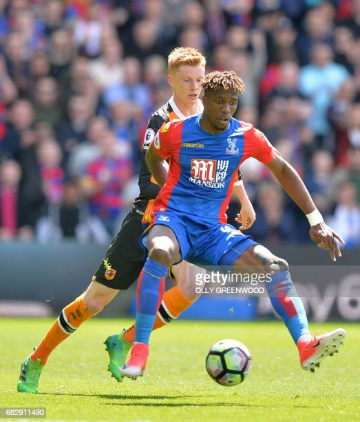 Crystal Palace's Ivorian striker Wilfried Zaha vies with Hull City's English midfielder Sam Clucas during the English Premier League football match...