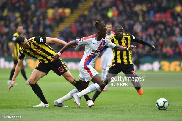 Crystal Palace's Ivorian striker Wilfried Zaha vies with Watford's Northern Irish defender Craig Cathcart and Watford's French midfielder Abdoulaye...